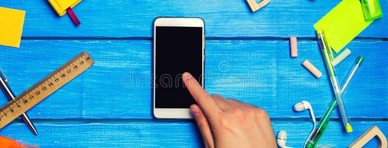 Studentpunkter till telefonen, den digitala dagboken eller eBooken, motvillighet som ska l?ras, skolatillf?rsel p? en bl? bakgrun arkivfoton