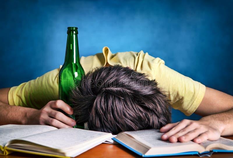 Studentsömn med ett öl royaltyfri bild