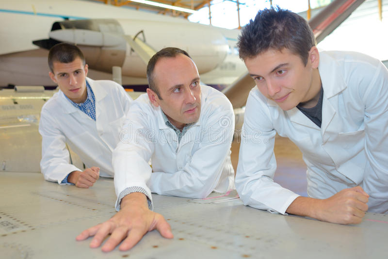 Students in aircraft hangar looking at plan fuselage stock photo