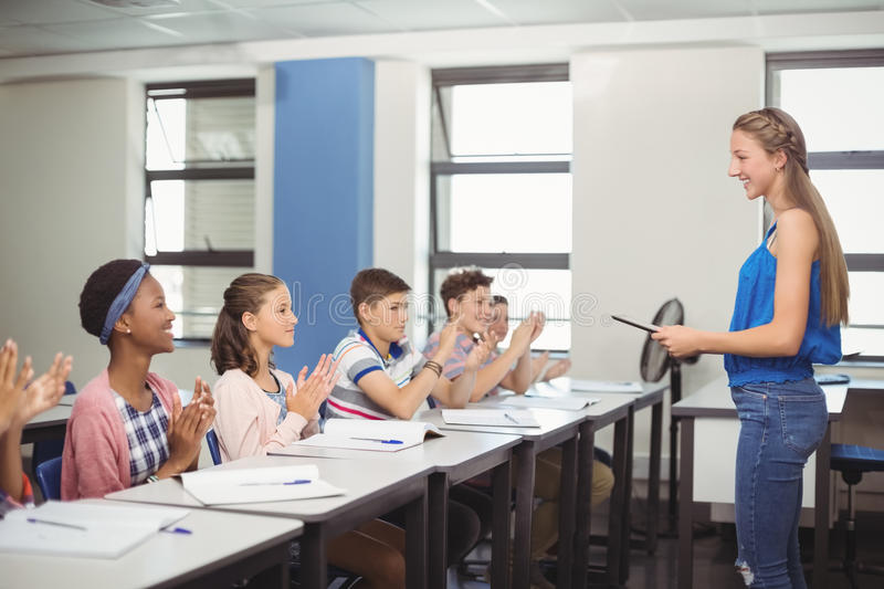 Students appreciating classmate after presentation in classroom. At school royalty free stock photo