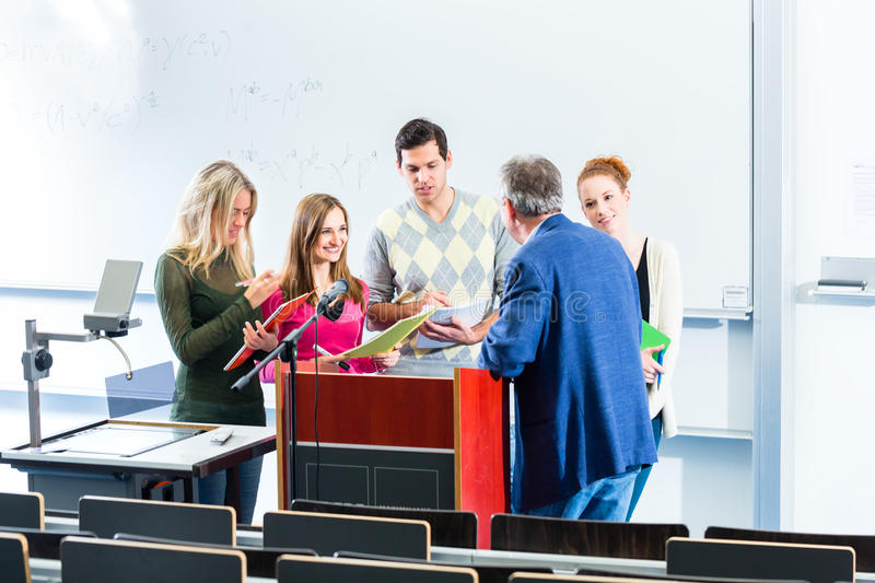 Students asking professor in college auditorium royalty free stock images