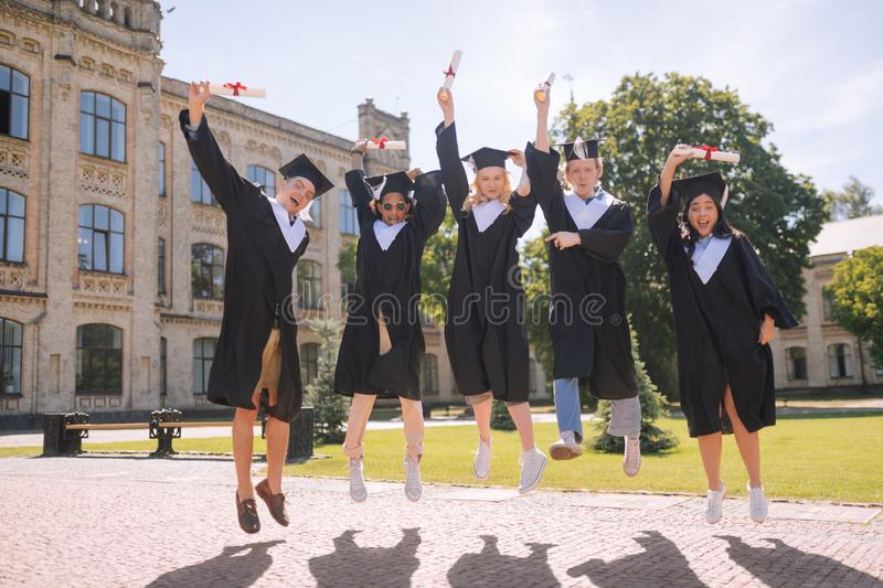 Students being excited graduating the university together. stock photo