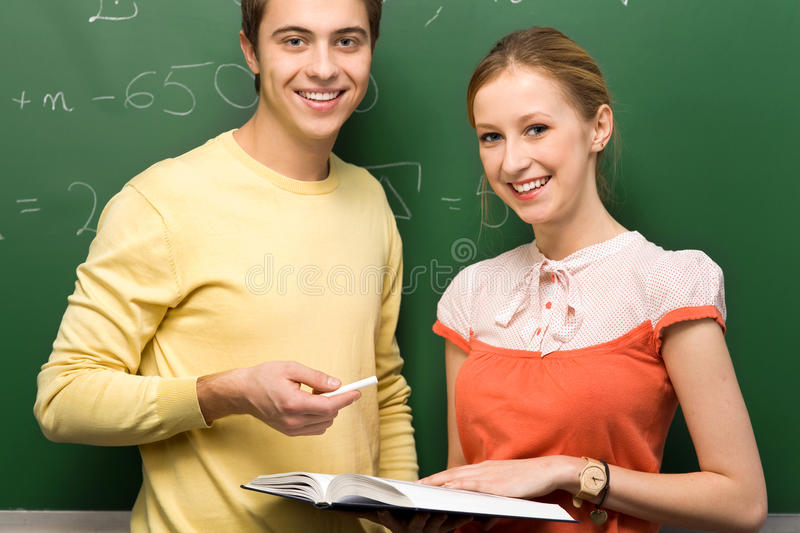 Students by blackboard. Two students standing next to blackboard stock image