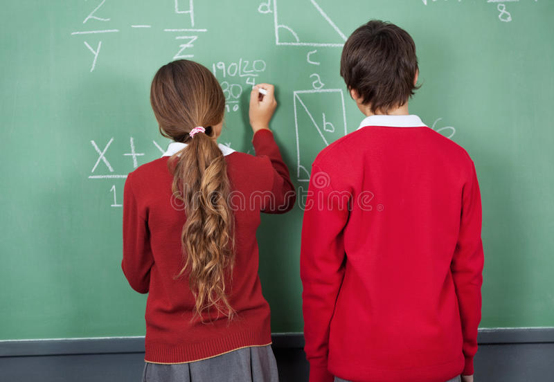 Students at blackboard. Rear view of teenage girl writing on board with classmate standing in classroom stock photo