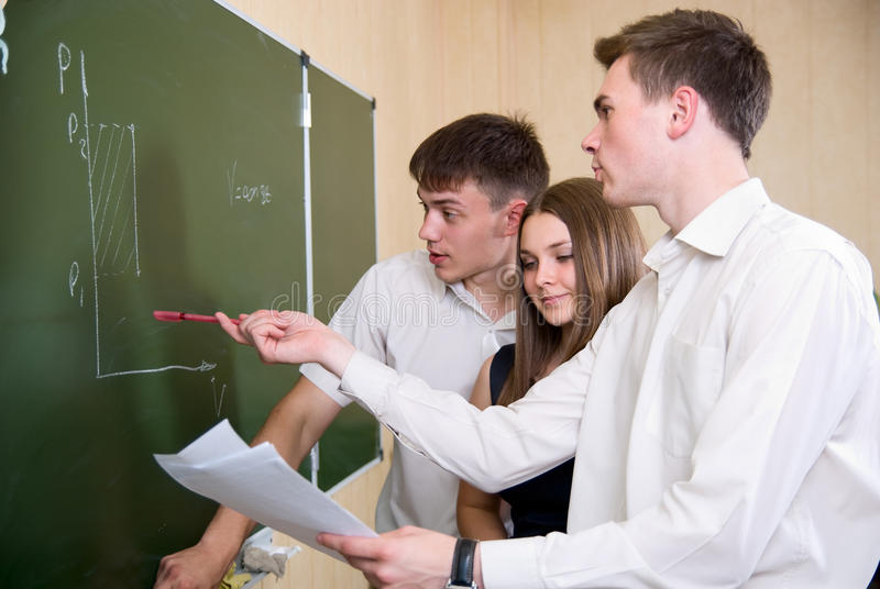 Students at a board solve a problem stock photos
