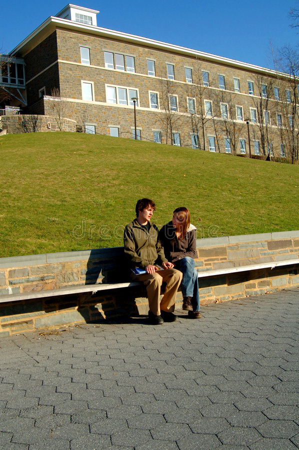 Students on campus. Two students sitting on a bench talking at university stock photo