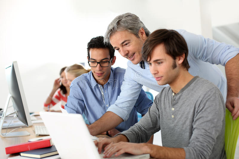 Students in classroom with professor helping them stock images