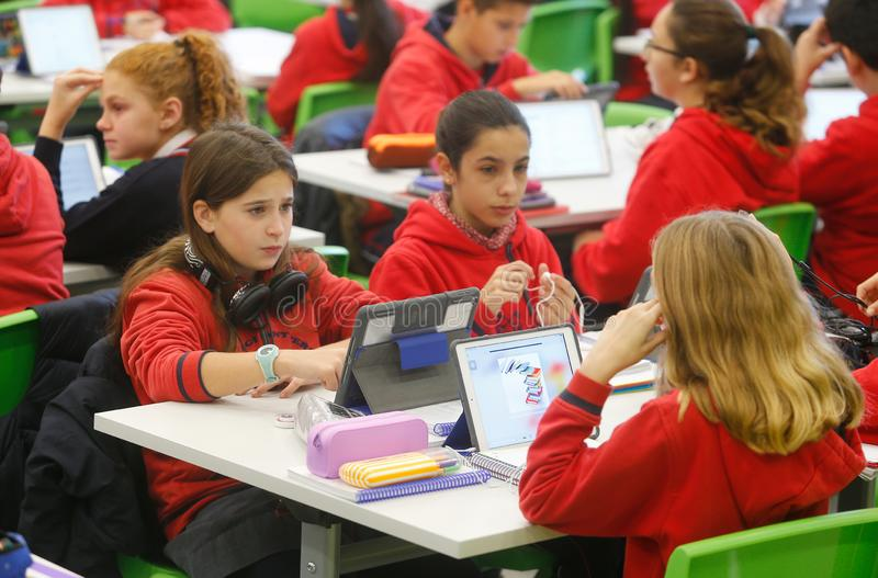 Students in classroom sing technology. Students in their classroom in a school in Palma de Mallorca testing a pilot experience creating huge classes with more stock image