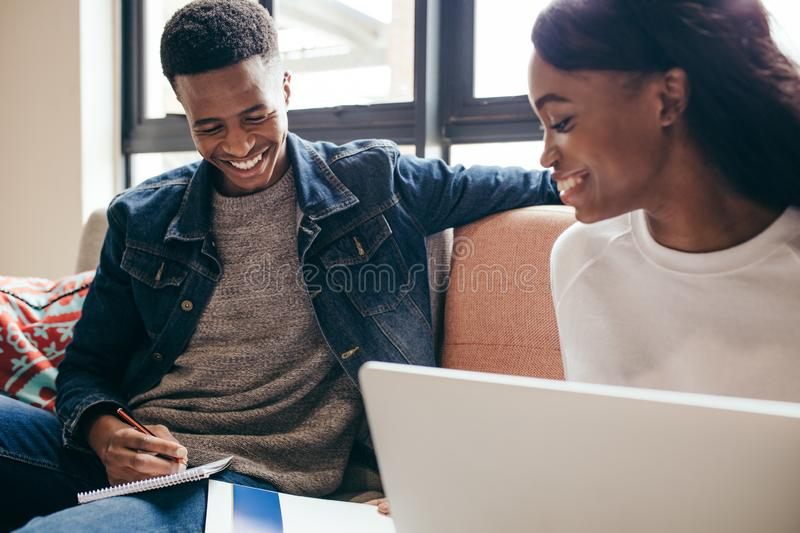 Students completing their class assignment. African girl reading book with her classmate making notes sitting on sofa at college. Two young people completing royalty free stock images