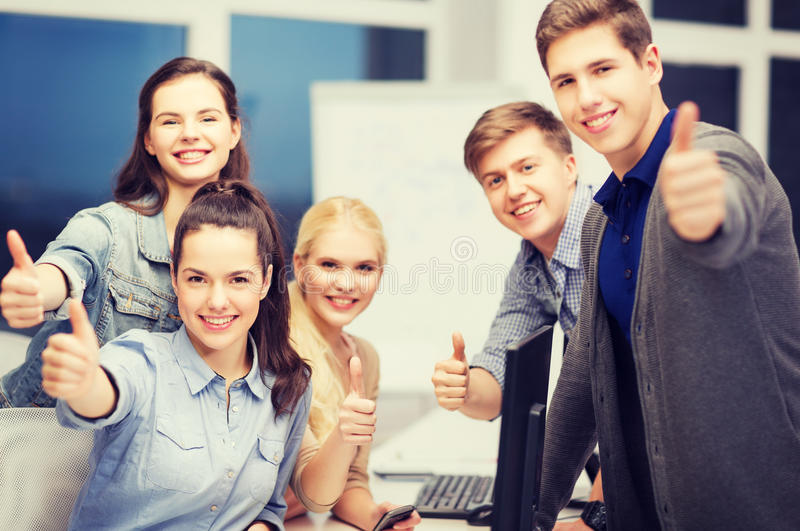 Students with computer monitor and smartphones. Education, school and people concept - students with computer monitor and smartphones showing thumbs up royalty free stock photo
