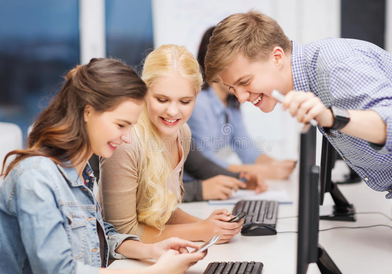 Students with computer monitor and smartphones. Education, techology and internet concept - group of smiling students with computer monitor and smartphones stock photos