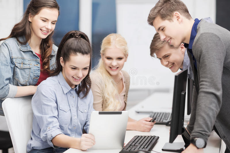 Students with computer monitor and tablet pc. Education, technology and internet concept - students with computer monitor and tablet pc royalty free stock images