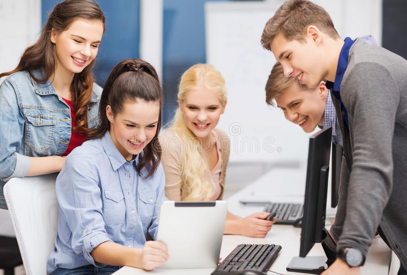Students with computer monitor and tablet pc. Education, techology and internet concept - group of smiling students with computer monitor and tablet pc royalty free stock images