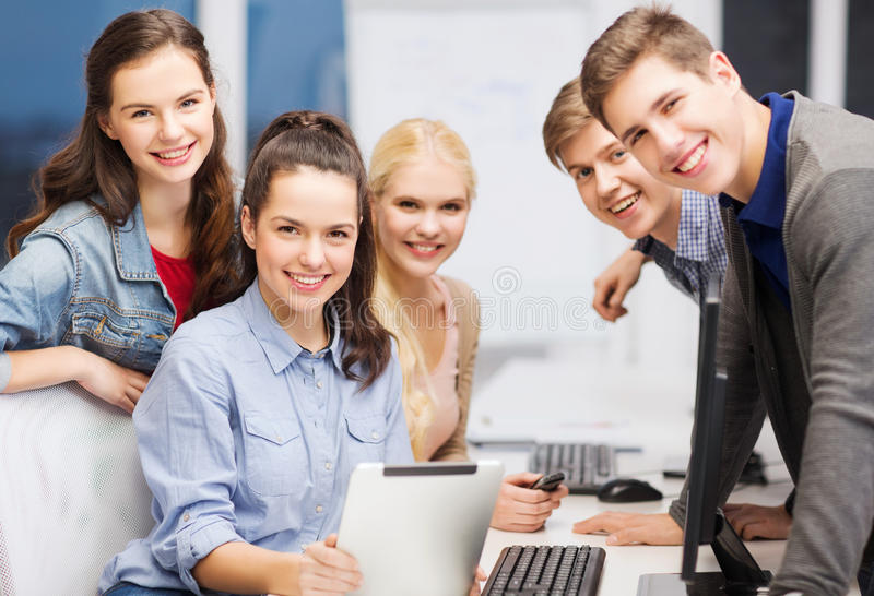 Students with computer monitor and tablet pc. Education, techology and internet concept - group of smiling students with computer monitor and tablet pc stock photo