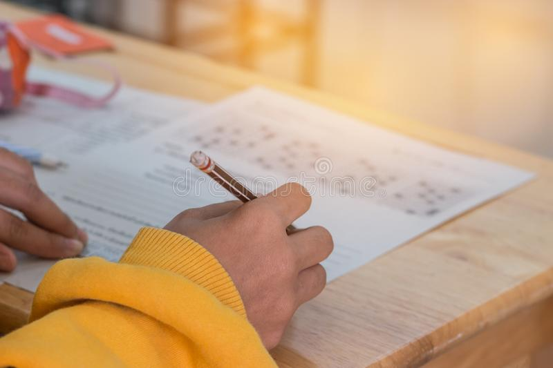 Students concentration holding pencils in hand doing multiple-choice quizzes testing exams answer sheets exercises in. School, Tests is concept assessment royalty free stock images