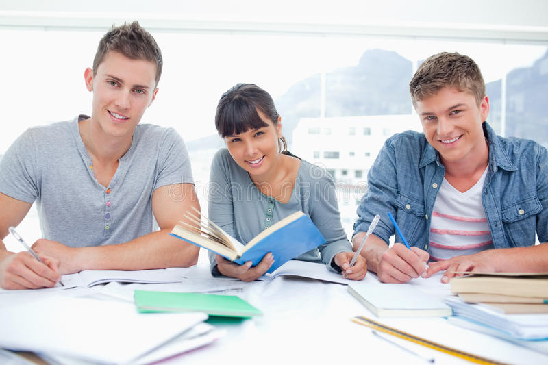 Students Doing Work Together As They All Look Into The Camera Royalty Free Stock Photography