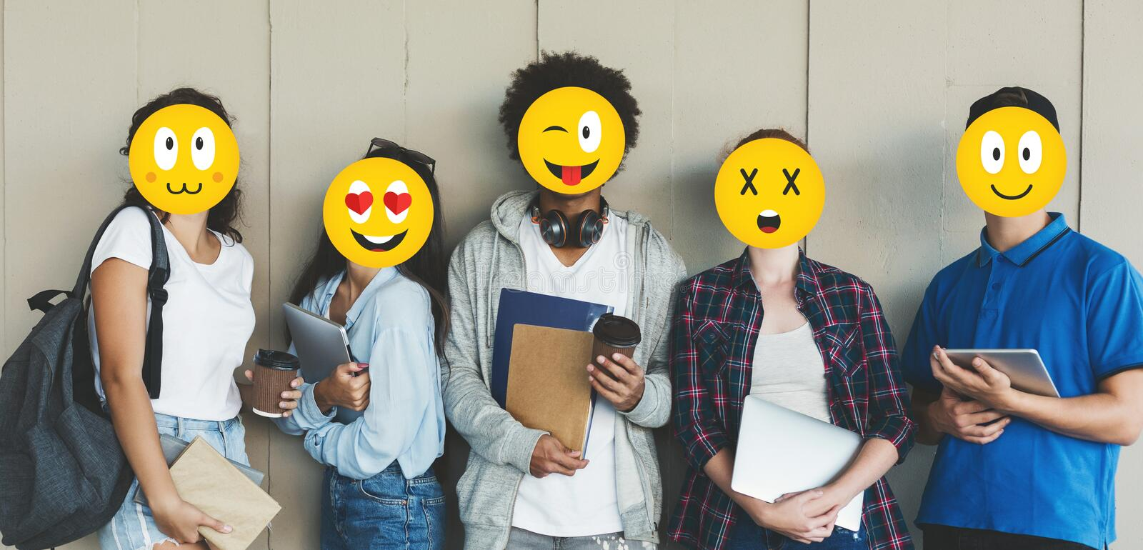 Students with emoji faces holding books over grey background. Panorama stock photography