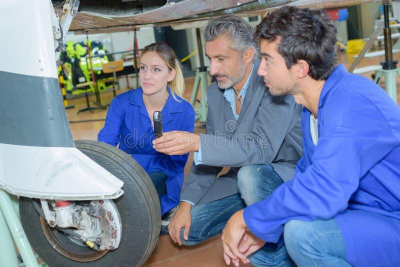 Students examining aircraft`s landing gear royalty free stock image