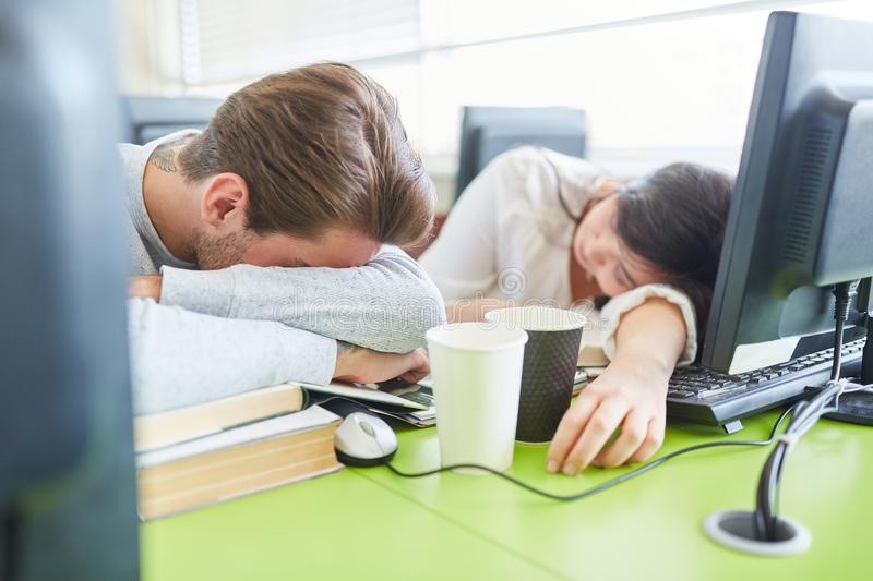 Students with fatigue sleep in front of computer. In university classroom stock photography