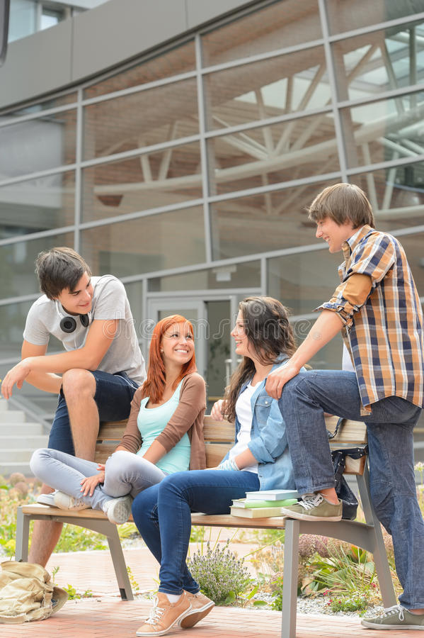 Students friends sitting bench front of university royalty free stock photos