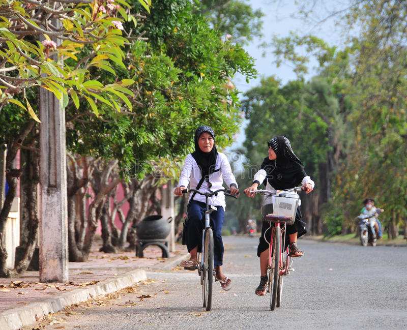 Students go to school by bike in Kampot, Cambodia.  stock photo