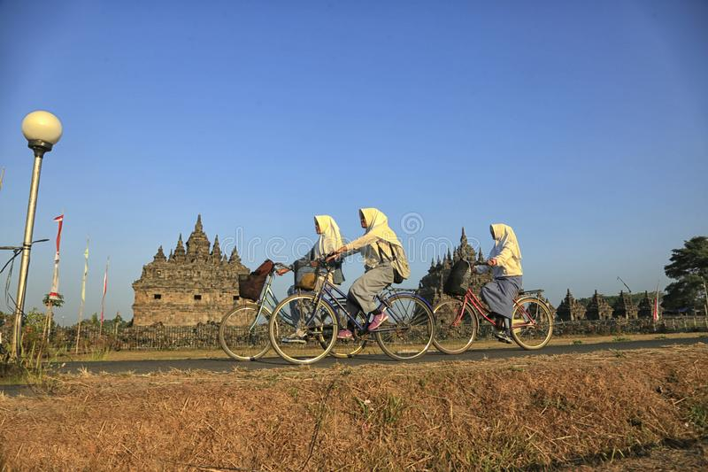 Bike to School. Students are going to school by bicycle across the Plaosan Temple area, Yogyakarta, Indonesia, on August 27, 2018 stock photos