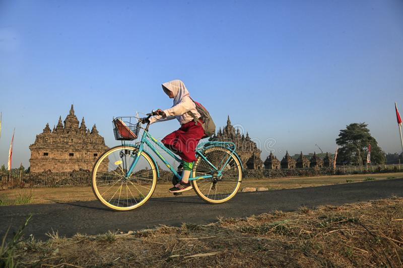 Bike to School. Students are going to school by bicycle across the Plaosan Temple area, Yogyakarta, Indonesia, on August 27, 2018 royalty free stock photos