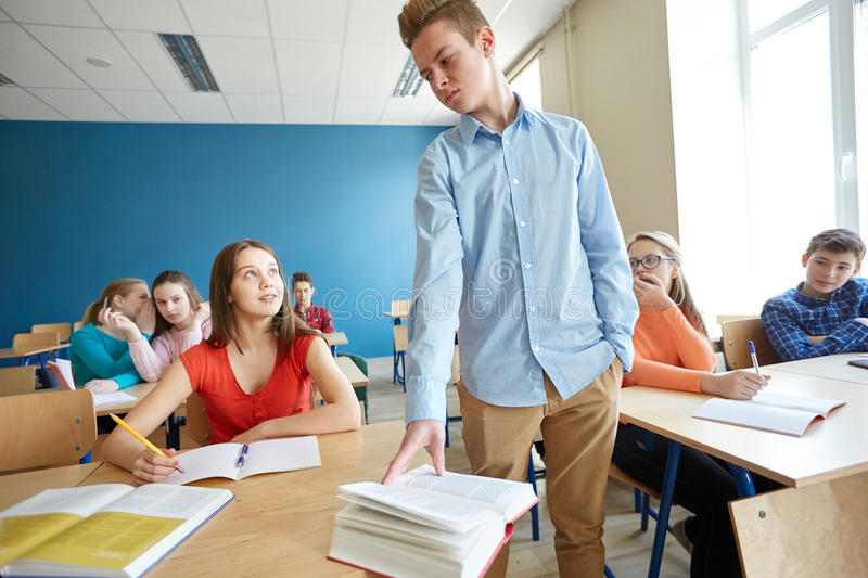 Students gossiping behind classmate back at school. Education, bullying, conflict, social relations and people concept - student boy behaving unfriendly to girl stock photos