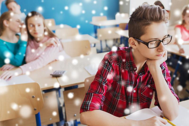 Students gossiping behind classmate back at school. Education, bullying, social relations and people concept - classmates gossiping behind student boy back at royalty free stock images