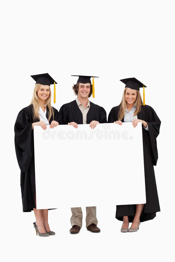 Students in graduate robe holding a blank sign