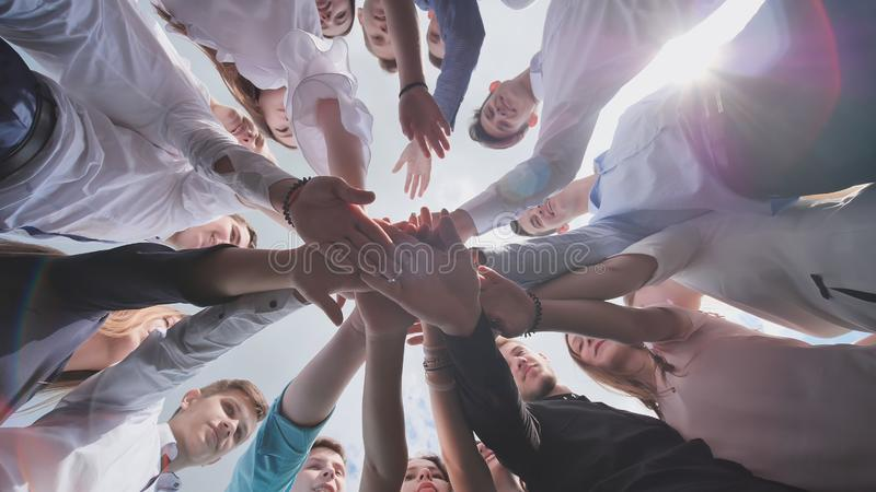 Students graduates gather around and lay their hands in a sign of successful work. royalty free stock photos