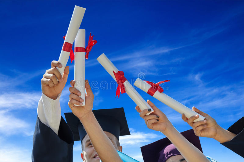 Students graduates with hats and diplomas. Graduates stutents throwing graduation hats in the air stock image