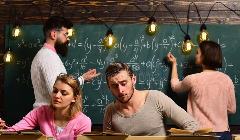 Students, group mates studying, while teacher asking girl near chalkboard. Exam concept. Bearded teacher, , professor royalty free stock photography