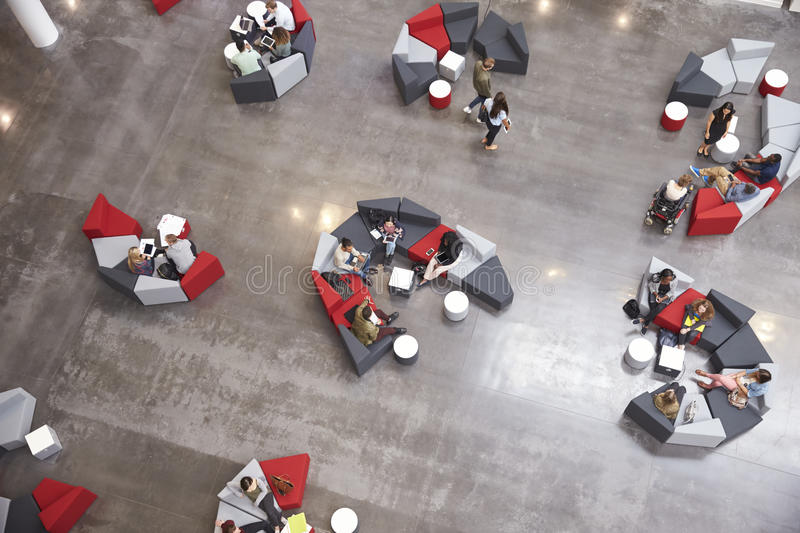 Students groups sitting in a modern university atrium stock photography