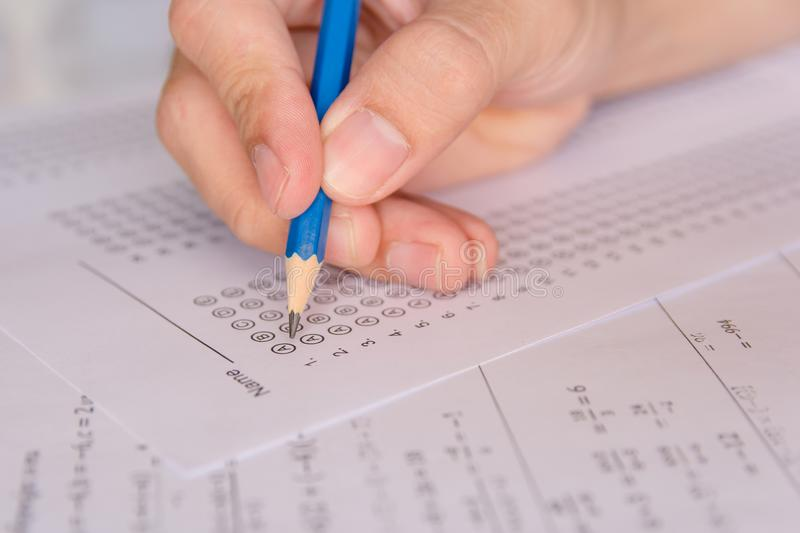 Students hand holding pencil writing selected choice on answer s stock images