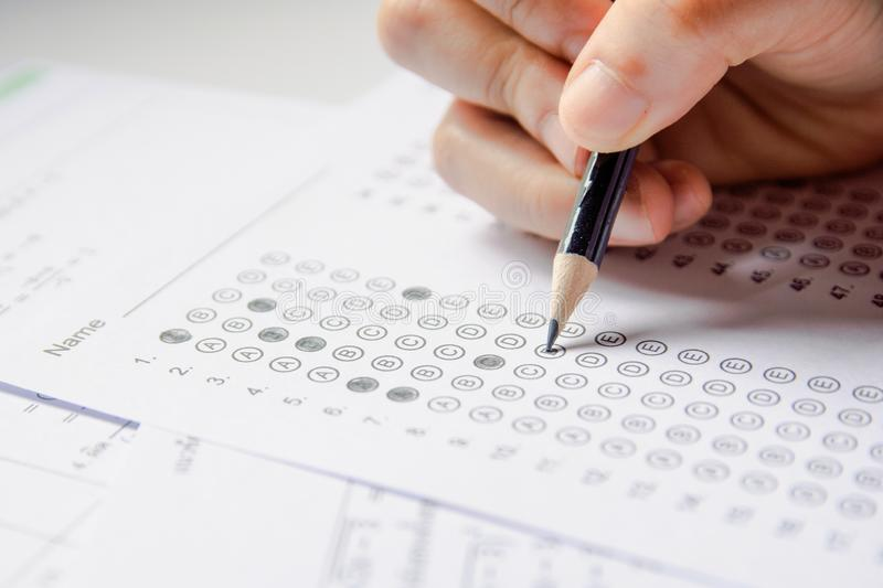 Students hand holding pencil writing selected choice on answer sheets and Mathematics question sheets. students testing doing stock images