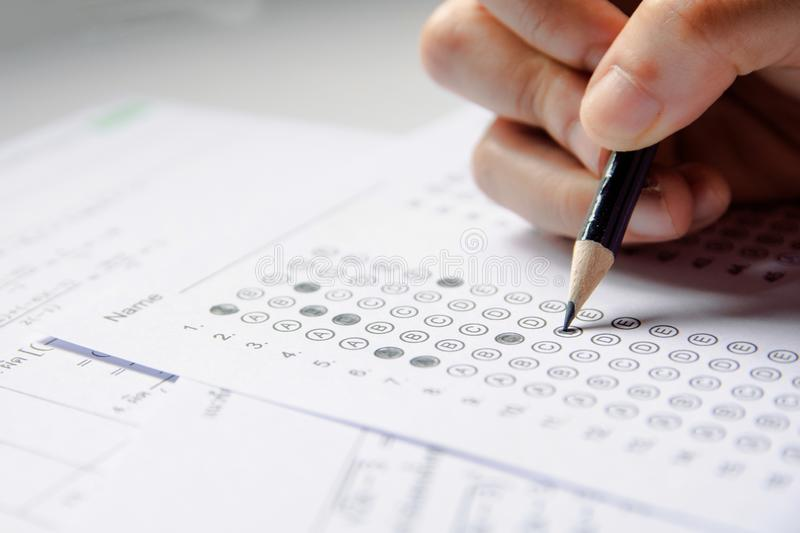 Students hand holding pencil writing selected choice on answer sheets and Mathematics question sheets. students testing doing royalty free stock photos