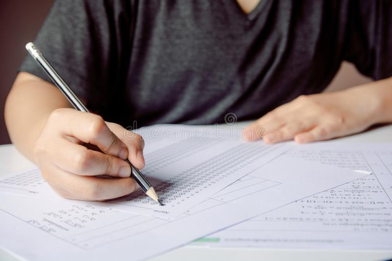 Students hand holding pencil writing selected choice on answer sheets and Mathematics question sheets. students testing doing royalty free stock photo