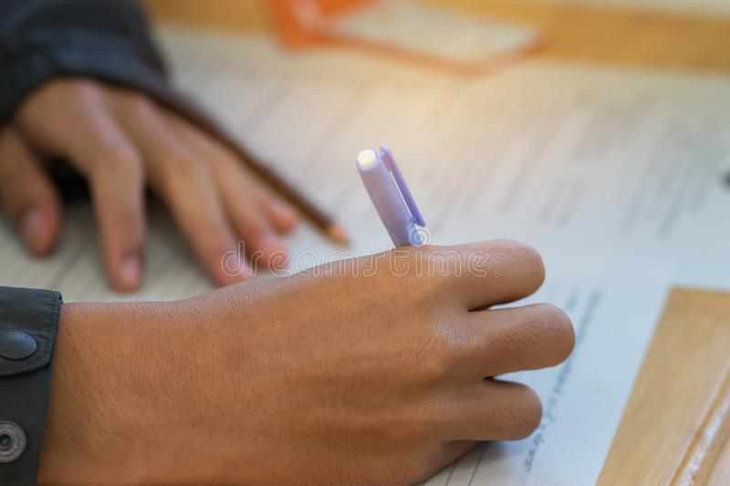 Students hands taking exams, writing examination room with holding pencil on optical form of standardized test with answers and e. Nglish paper sheet on row desk stock images