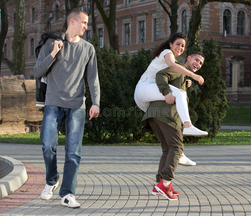 Students having fun. Group of young people having fun, men giving piggyback ride to a girl in student campus stock photo