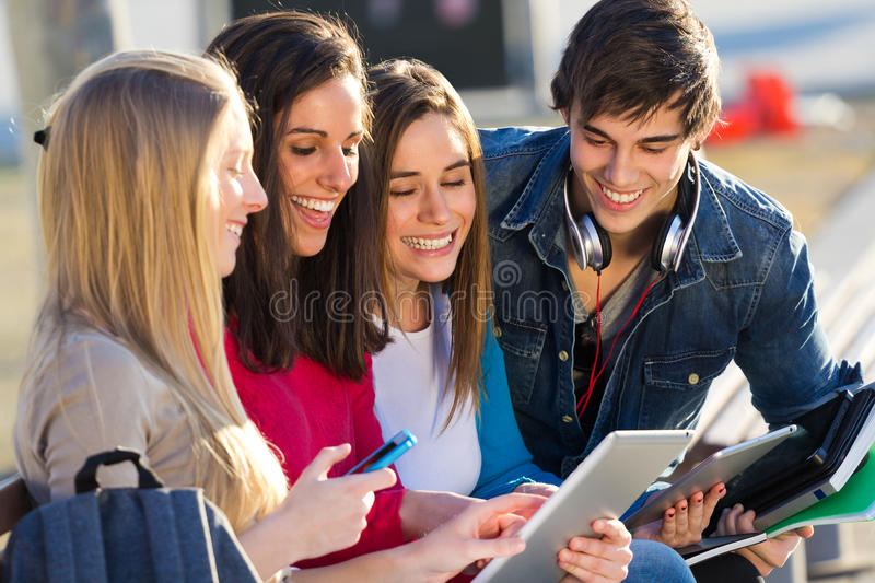 Students having fun with smartphones and tablets after class. A group of students having fun with smartphones and tablets after class royalty free stock images