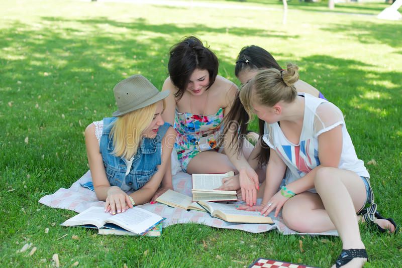 Students having lesson outdoor. Students read a book in the park stock photos