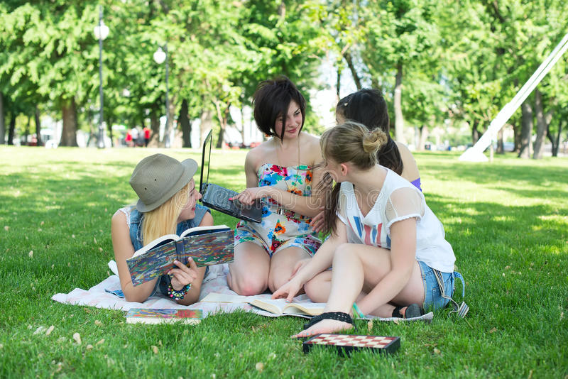 Students having lesson outdoor. Students read a book in the park stock photo