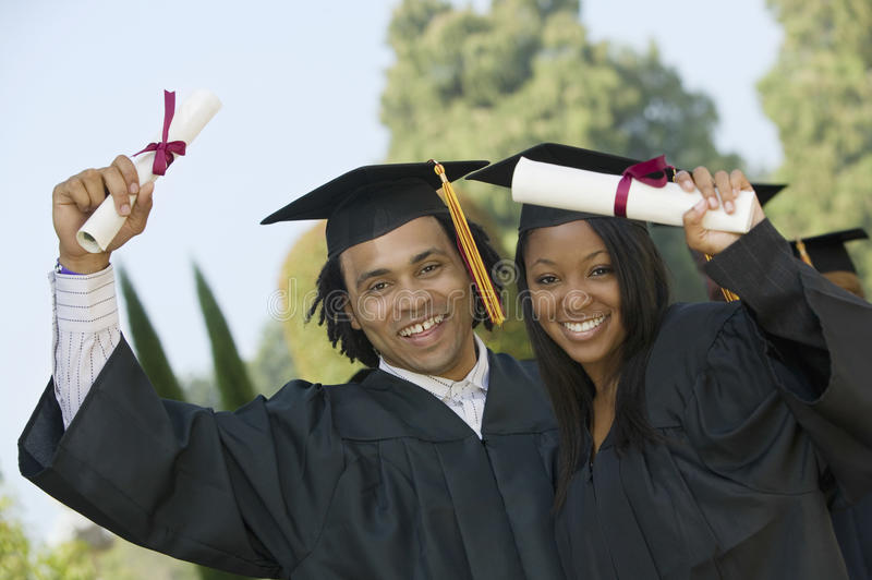 Students Holding Diplomas On Graduation Day stock photos
