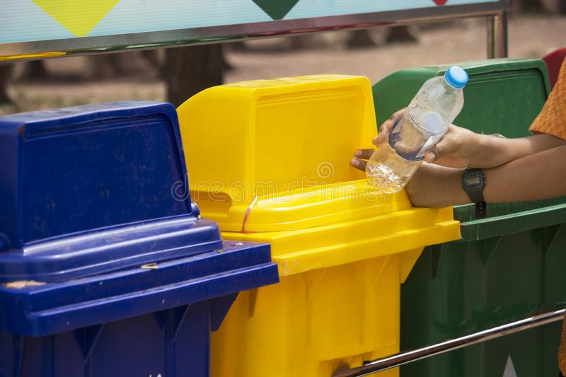Students are holding a plastic water bottle to put into the three-color trash bin. To sort out recyclable waste stock image