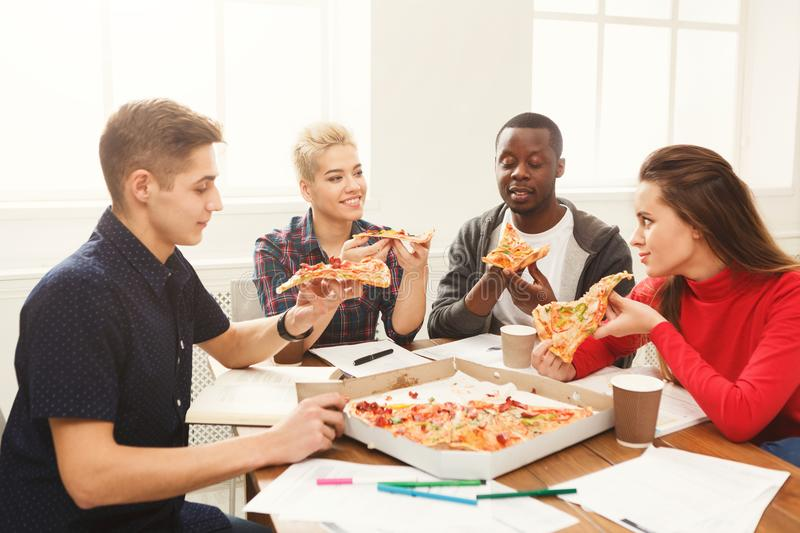 Students learning and eating pizza stock photos