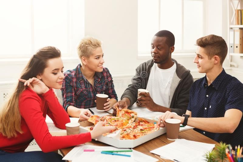 Students learning and eating pizza stock photo