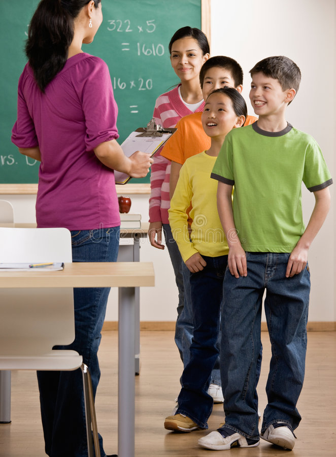 Students listen to teacher with clipboard royalty free stock photo