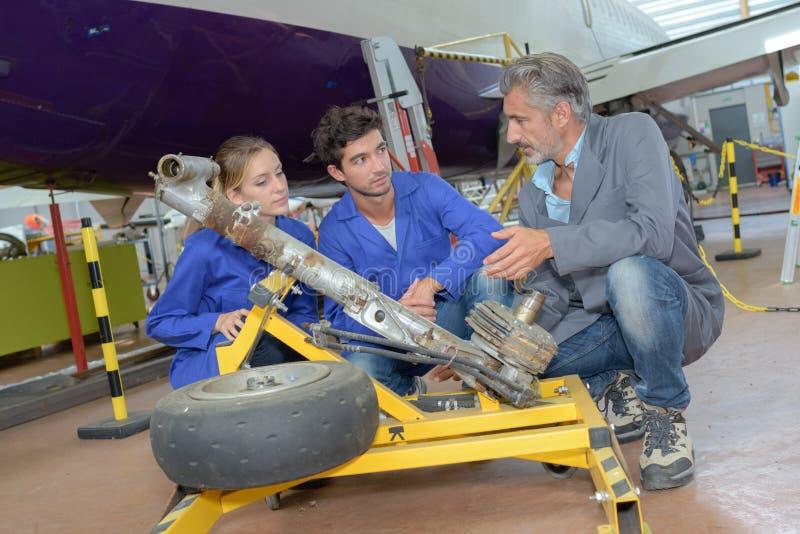 Students looking at aircraft landing gear royalty free stock photography