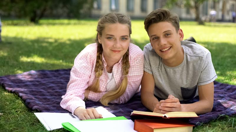 Students looking at camera, lying on plaid near university campus, studying royalty free stock images